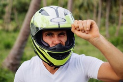 Close portrait of caucasian man in sport motorcycle green yellow helmet in tropical jungle at sunset light, front view