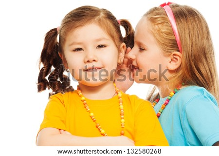 Close portrait of two little 6-7 years old Asian and Caucasian girls whisper telling secrets mouth to ear, isolated on white
