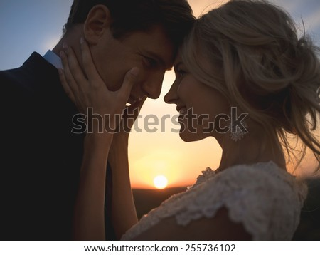 Close portrait silhouette in love wedding couple. Against the setting sun in the field. Lovers hug, girl tenderly holding her husband\'s face with both hands, smiling and looking into his eyes.