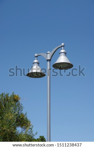 Close sectional upwards view of a public double street light with bell-shaped lamp shades