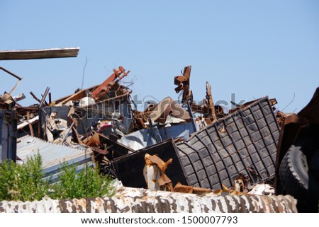 Close sectional view into a pile of scrapped vehicles and other materials and blue sky above