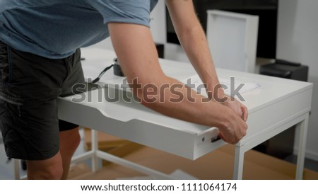 close shot at the man's hands, the person is engaged in assembling the table for the living room, he screws the bolts in the shelf, the piece of furniture is ready and decorates his cozy apartment