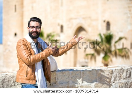 Close shot of a handsome man wearing a winter outfit and standing in front of the castle and showing it to the people #1099314914