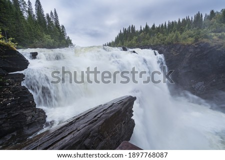 Close shot of a potent waterfall on a misty and rainy day. Tännforsen, the biggeset waterfall in Sweden. Rocks in the front, trees in the back. Foto d'archivio ©