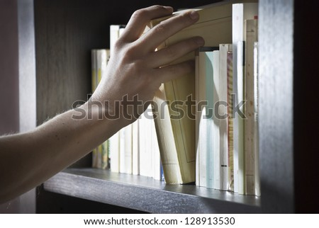 Close shot of a right hand of a young man picking a book in a bookshelf.