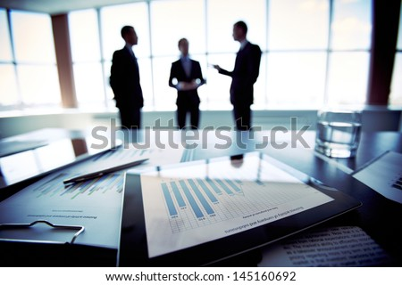 Close-shot of a tablet computer displaying financial data, three businessmen standing in the background
