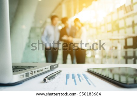 Close-shot of a tablet computer displaying financial data, three businessmen standing in the background #550183684