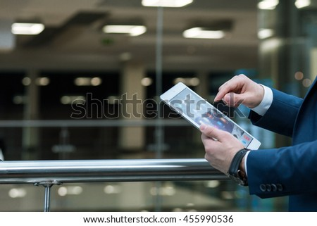 Close shot of an elegant man's hands holding a tablet, close to the railing #455990536
