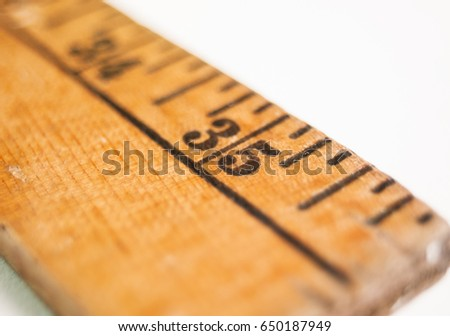 Close shot of an old yardstick showing the number 35.  Low angle with shallow depth of field.