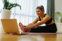 Close shot of blonde fit woman making forward fold yoga exercise while sitting on mat at home. Young woman is watching online yoga course due to COVID 19 pandemic.