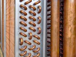 Close shot of copper plain tubes of a condenser coil.