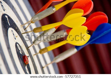 Close shot of red, yellow and blue darts stuck in a dart board but not in the bulls eye