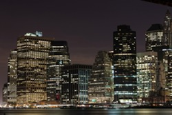 Close shot of skyscrapers with lights on in the offices by night, Manhattan, New York.
