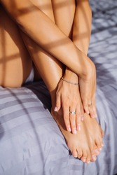 Close shot of womans hand with jewerly, bracelets and rings, hold legs. Woman sit on stripped gray blanket in bedroom at sunset light
