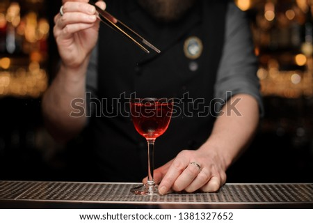 Close shot of young male bartender dropping small cherry from special forceps in an alcohol drink #1381327652