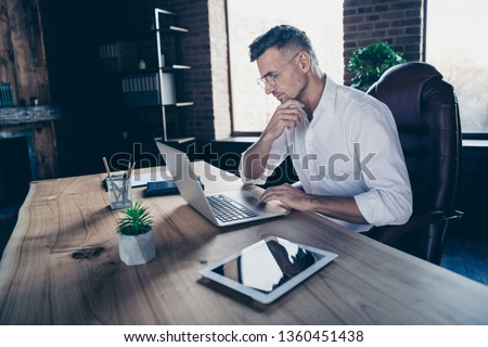 Close side profile up photo handsome he him his macho guy ponder pensive having online currency business chat letters attentive notebook table sit big office chair wear specs formal-wear white shirt
