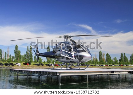 Close side view of a small civil helicopter standing on a helipad on a water dock. Warm summer day, blue sky and white clouds. Luxury lifestyle, travel, emergency air transportation concept.