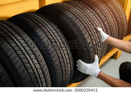 Close to the hands of a tire changer in Large warehouse of car tires, rack with customer car tires in warehouse of a tire dealer