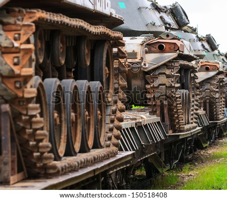 Close-trains carrying military tanks outdoors.