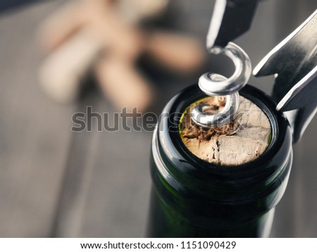Close uo of a wine bottle with bottle opener on a dark background Stock photo ©