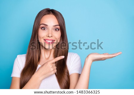 Close uo photo of cute youth holding hand showing adverts wearing white t-shirt isolated over blue background