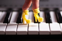 close-up a child's hand with fingers stuck in a toy yellow high-heeled doll's shoes steps on the piano keys