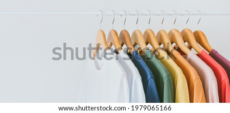 Close up a collection of pastel color t-shirts hanging on a wooden clothes hanger in closet or clothing rack over white background, copy space Zdjęcia stock ©