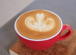 Close up a cup of coffee red color cup with hot latte art in heart shape on wooden trey with blurred background, milk foam, stream milk.