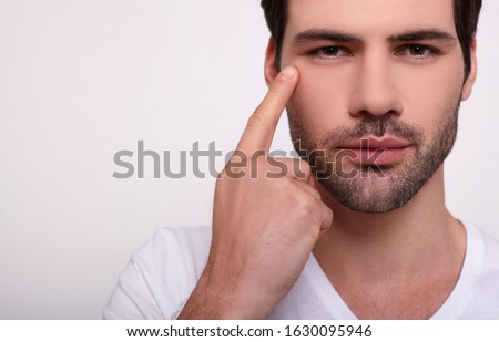 Close-up, a handsome handsome dreamy young Caucasian man with dark hair, brown eyes, delicate bristles, points his finger at his right eye. The guy does skin care treatments. Copy space.