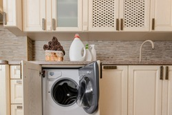 Close up a laundry basket full with fresh clean towels near bottle of liquid detergent powder wash, bleach, spray on  stone table near wash machine. Vintage wood kitchen background
