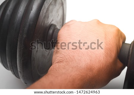 Close up a man hand is holding black dumb bell over white background. Dumb bell is an equipment of build up muscle.