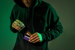 Close-up: a man in a black hoodie is holding a stolen plastic credit card. Theft of electronic money. Financial crisis.