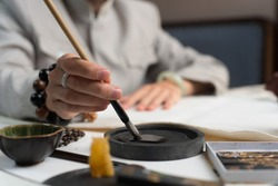 close up. A man in a gray jacket dips a brush in ink for traditional Chinese writing - calligraphy.
