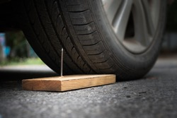 Close up a metal nail on board wood nearly to puncture into wheel tire