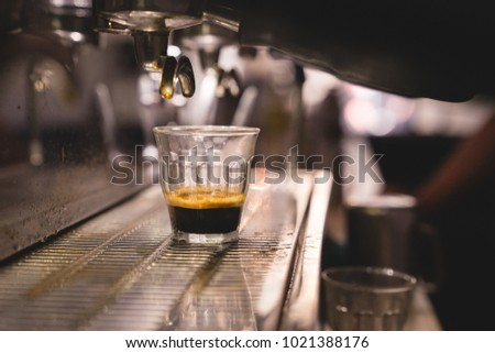 close up a piccolo clear grass under an espresso machine with group handle in cafe #1021388176