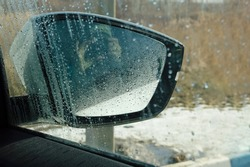 close-up - a silhouette of a woman in the side mirror of a car, seen through a window with water drops and drips