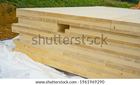 CLOSE UP: A stack of CLT wall panels lie uncovered at a construction site of a modern housing project made of a sustainable materials. Wind blows white tarp off the glued-laminated timber wall boards. Stok fotoğraf ©