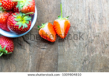 close up a strawberry slice on the wood floor and strawberry in a bowl white. selective focus with copy space #1009804810