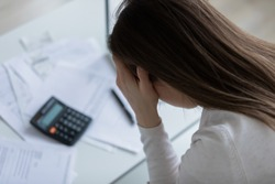 Close up above top view woman holds her head with hands feels desperate after calculating expenses having financial problems, lack of money pay bills domestic household utilities, high taxes concept
