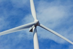 Close up abstract view of a giant wind turbine with blue sky background