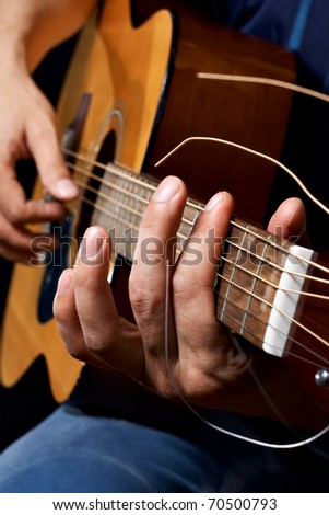 Close up acoustic guitar in musician hands in dark room