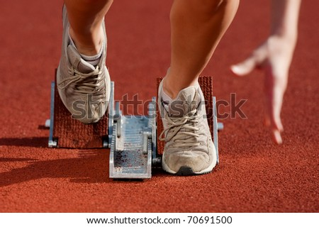 Close up, action packed image of a female athlete leaving the starting blocks for a sprint run on a track