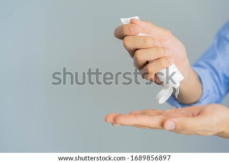 close up adult man squeeze on sanitizer gel tube product to washing and rubbing hand to cleaning for protect virus and prevent coronavirus (MERS-n COV) and bacteria concept Stock foto ©