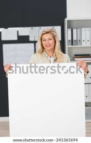 Close up Adult Office Woman Standing Behind Clean White Board at the Office.Captured her While Looking and Smiling at the Camera.