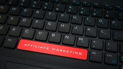 Close-up AFFILIATE MARKETING text on spacebar button with red color on a black laptop keyboard background. Business strategies concept. Selective focus.