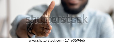 Close up African agent reach out hand to camera handshake client. Make deal, company boss HR recruiter greet applicant starting job interview concept. Horizontal photo banner for website header design