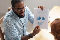 Close up African American businessman consulting client, holding document with graphs and diagram, mentor explaining business strategy to trainee, partners discussing project results