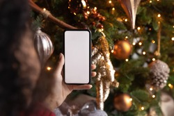 Close up African American woman holding phone with empty white screen mockup near decorated festive tree, celebrating Christmas, customer shopping online, purchasing gifts, browsing gadget apps