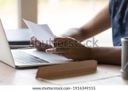 Close up African American woman reading letter at home, sitting at table with open envelope and laptop, businesswoman working with correspondence, received information from bank or college Сток-фото ©