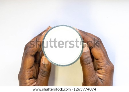 Close up African Woman's Hand holding glass of warm fresh milk on white background. Top view food and drink for healthy concept. good calcium nutrition drink in the morning,